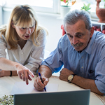 Woman and older man reviewing papers together, with women pointing to something on the page