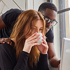 Woman drinking from a mug and looking intently at something with man peering over her shoulder